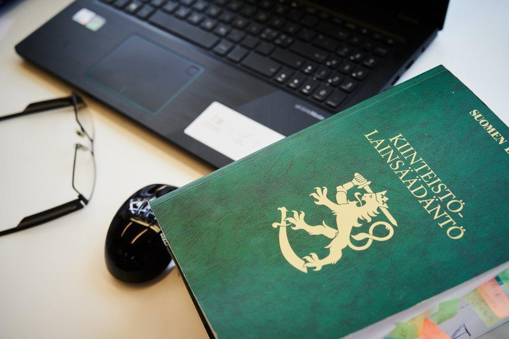 Lakikirja, kannettava tietokone ja silmälasit pöydällä.