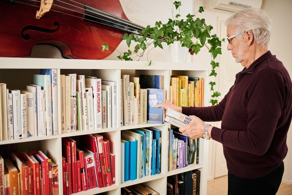 Mies valitsee kirjahyllystä kirjaa, hyllyn päällä lepää sello