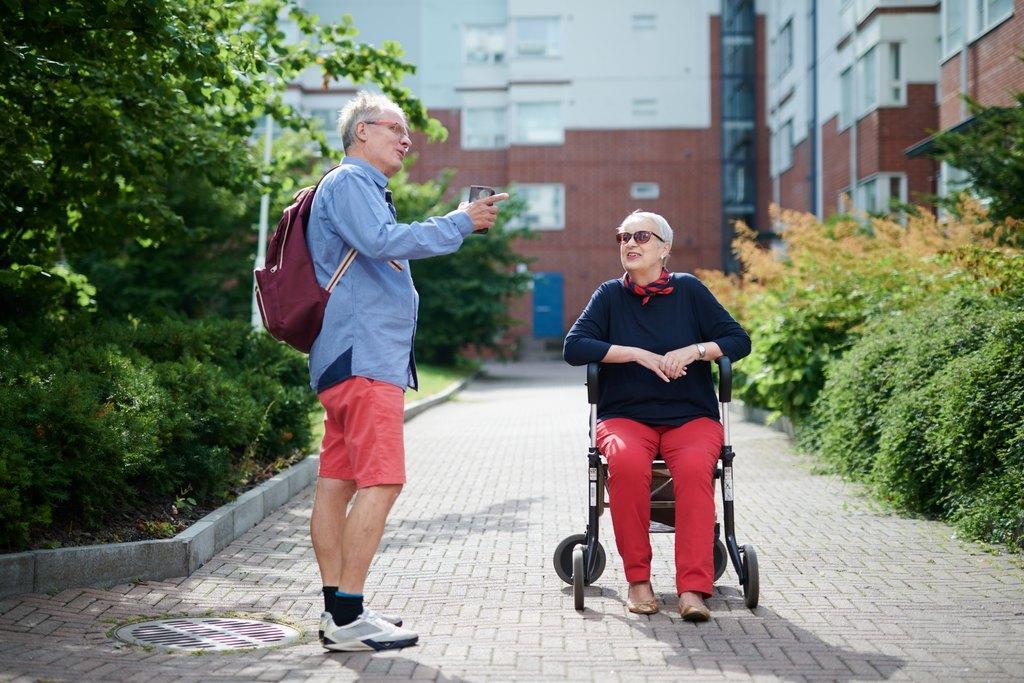 Mies ja nainen juttelevat ulkona, nainen istuu rollaattorin päällä, kerrostalon pihalla