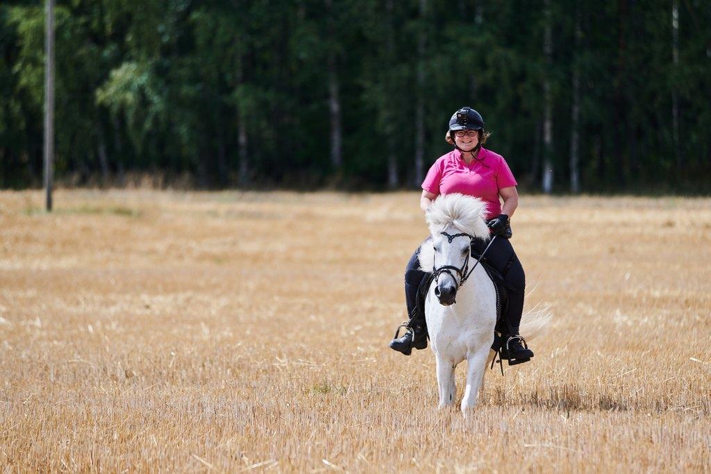 Nainen ratsastaa iloisena islanninhevosella sänkipellolla