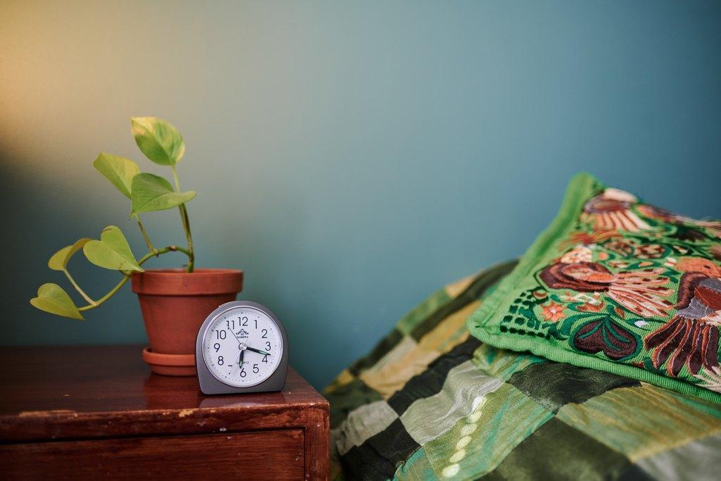Kello ja kukka yöpöydällä