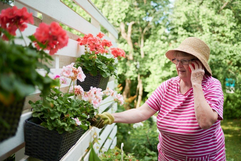 Nainen puhuu puhelimessa ystävälleen kukkaistutusten äärellä