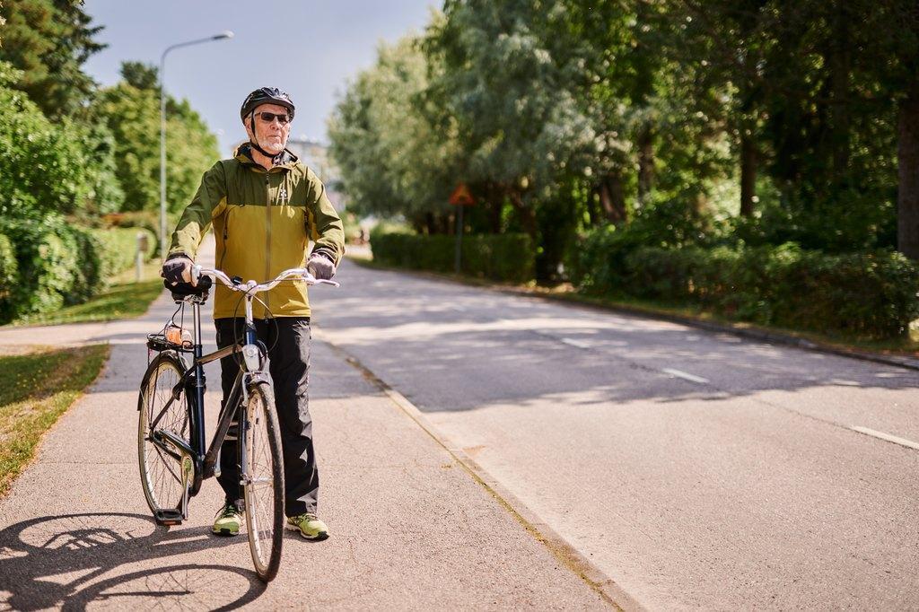 Vanhempi mies pyörän kanssa liikkeellä kauniina kesäpäivänä