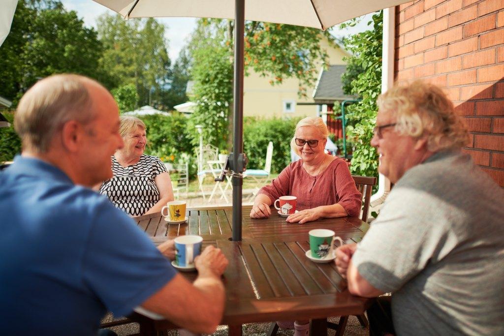 Iloisia ihmisiä kahvilla pöydän ääressä