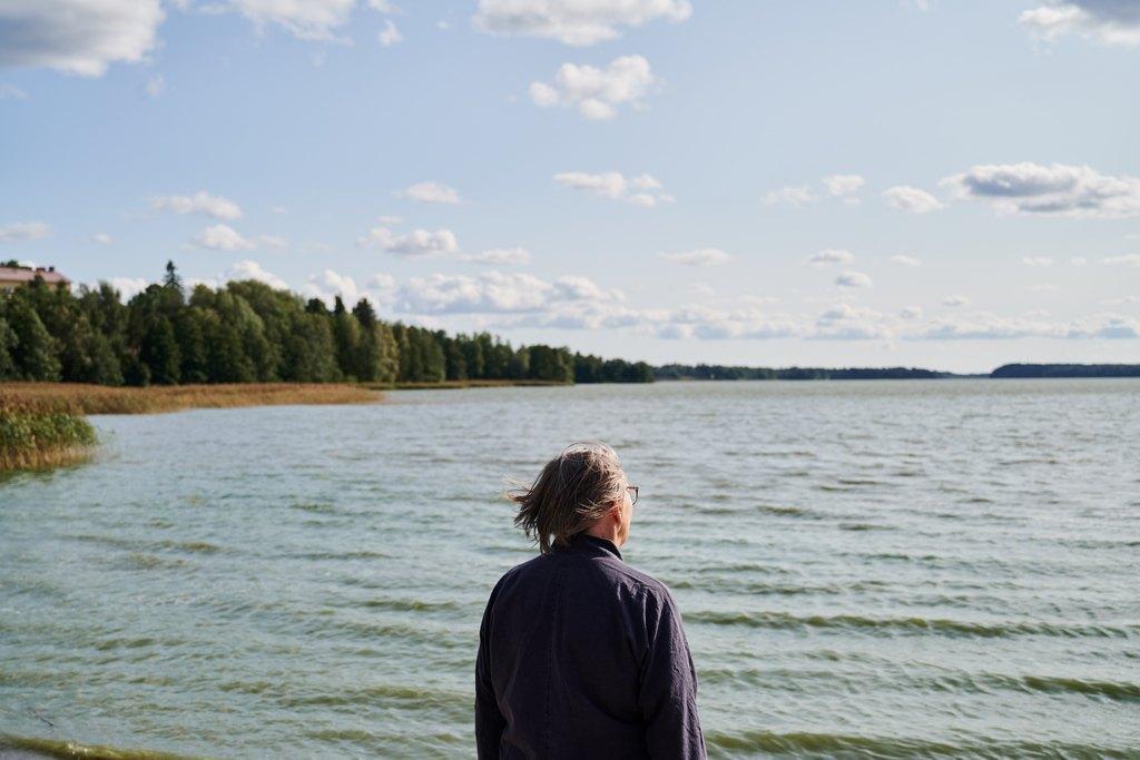 Harmaahiuksinen henkilö katselee edessään avautuvaa aaltoilevaa järvenselkää.