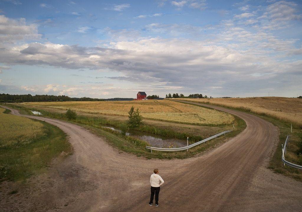 Maalaismaisema, jossa nainen etualalla katselee haarautuvaa tietä.