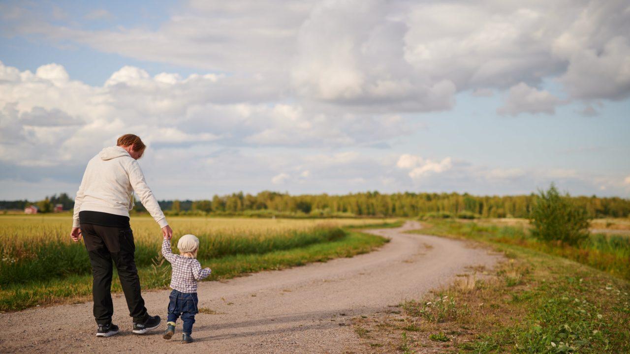 Nainen ja pikkulapsi kävelevät polulla, kuvituskuva