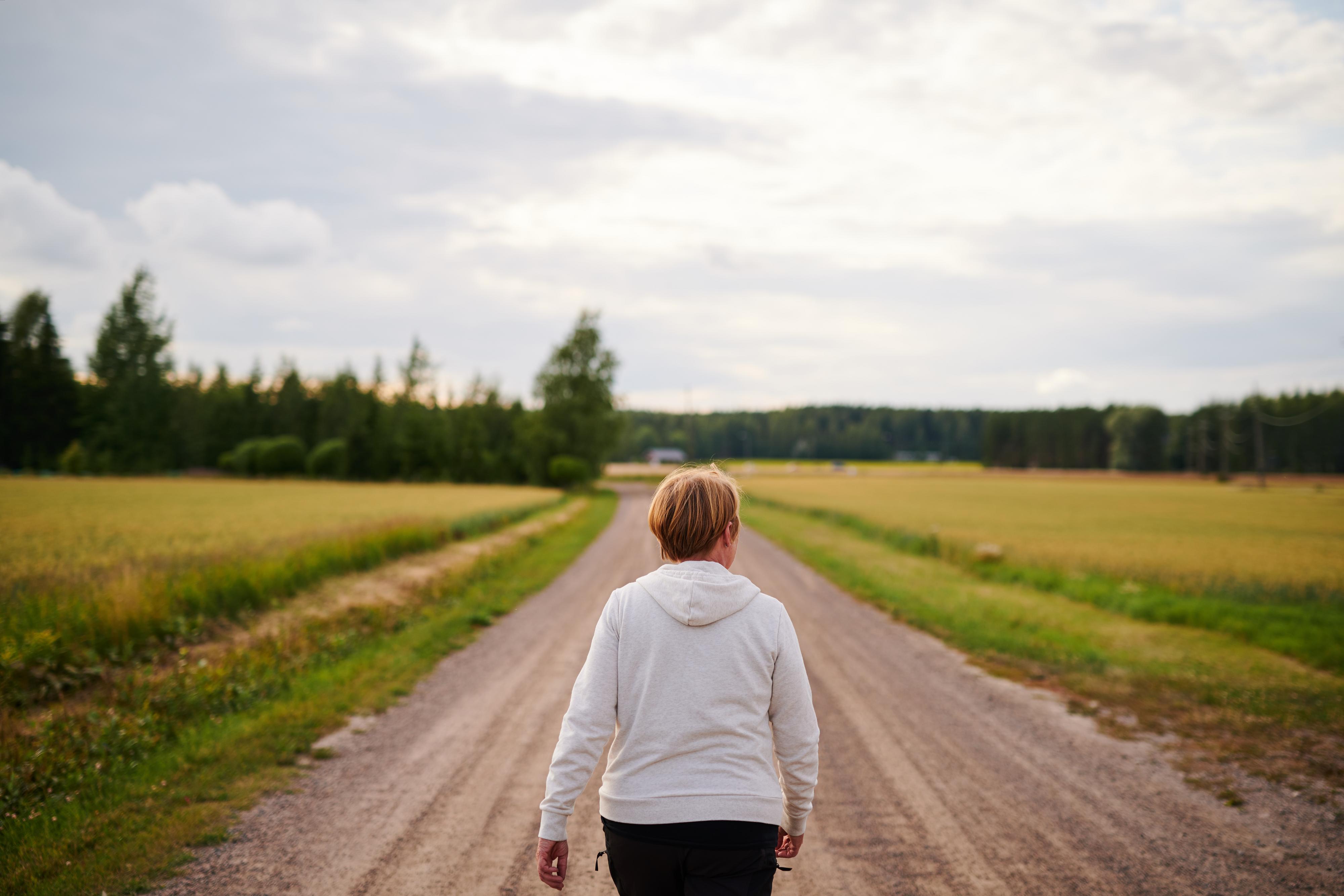 peltomaisemaa, nainen kävelee polkua pitkin